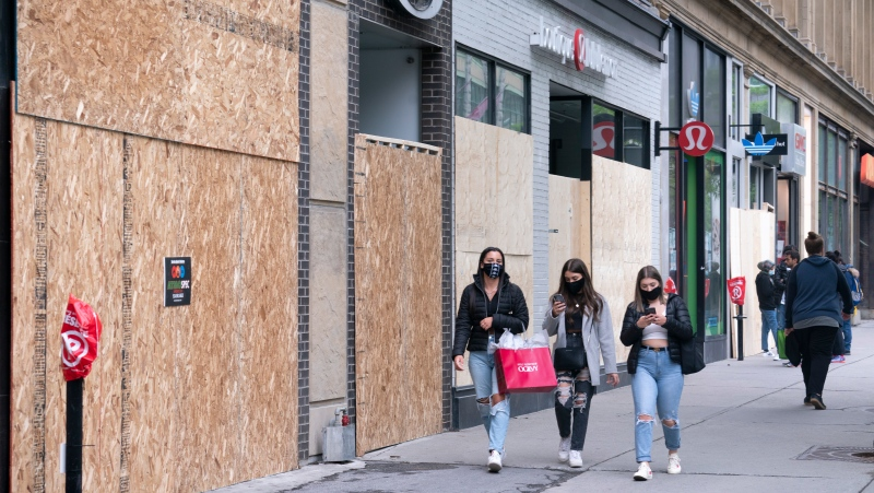 Shoppers walk past boarded up stores on Montreal's Sainte-Catherine street on Wednesday, June 3, 2020. THE CANADIAN PRESS/Paul Chiasson