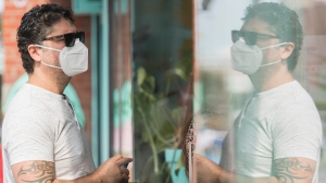 A man wears a face mask as he orders from a cafe in Montreal, Monday, September 7, 2020, as the COVID-19 pandemic continues in Canada and around the world. THE CANADIAN PRESS/Graham Hughes