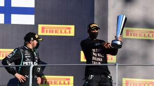 Winner of the race, Mercedes driver Lewis Hamilton of Britain, right, hoists the trophy as he stands with second place Mercedes driver Valtteri Bottas of Finland on the podium during the Formula One Grand Prix of Tuscany, at the Mugello circuit in Scarperia, Italy, Sunday, Sept. 13, 2020. (Jennifer Lorenzini, Pool via AP)