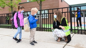 Five year-old Maverick Denette, centre, and his six year-old sister Peyton Denette, left, talk with a teacher as they return to school for their first day at St. Thomas More Elementary School in Mississauga, Ont., on Wednesday, September 9, 2020. THE CANADIAN PRESS/Nathan Denette