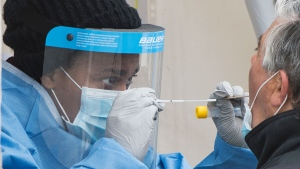 A health-care worker prepares to swab a man at a walk-in COVID-19 test clinic in Montreal North, Sunday, May 10, 2020. (THE CANADIAN PRESS/Graham Hughes)