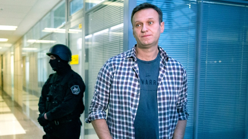 In this Dec. 26, 2019, file photo, Russian opposition leader Alexei Navalny speaks to the media in front of a security officer standing guard at the Foundation for Fighting Corruption office in Moscow, Russia. (AP Photo/Alexander Zemlianichenko, File)