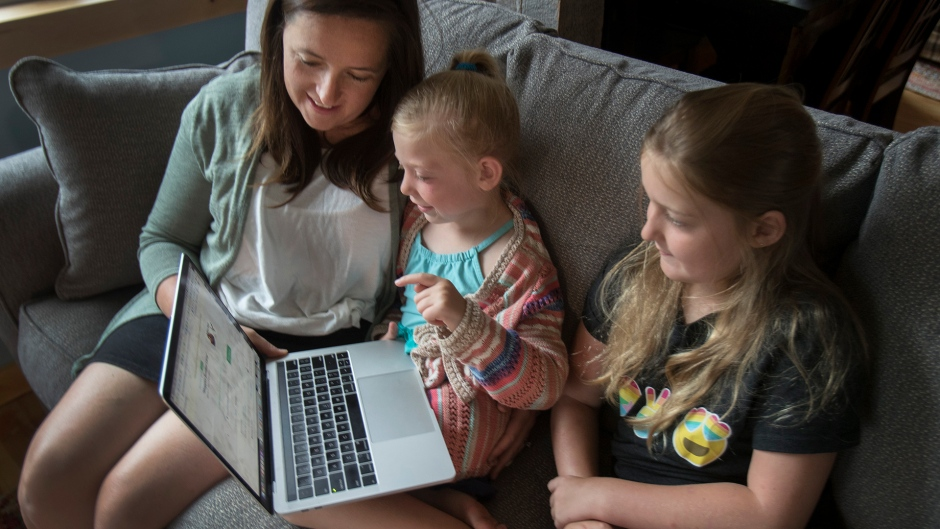 """Andrea MacDonald with her daughters Rose, 5, and Grace, 9, take part online with Twitter's """"virtual camp"""" at their summer residence in Harcourt, Ont., Sunday, August 2, 2020. When Andrea MacDonald begins working from home each morning, keeping her two daughters busy is rarely a worry. Grace and Rose have spent the last two months being read Dr. Seuss books by Twitter Inc. founder Jack Dorsey and learning about literary terms through Harry Potter. Both are part of Camp Twitter, a virtual program for kids of the tech company's employees. The offering is one of several dreamed up by companies to help Canadian employees juggle their professional and parenting duties, while working from home and having limited camps, daycare, school or child care options to lean on during the COVID-19 pandemic. THE CANADIAN PRESS/Fred Thornhill"""