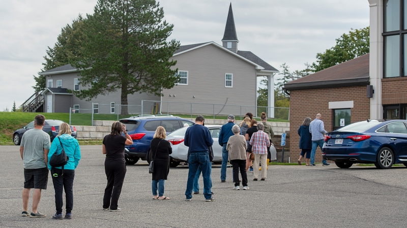 Residents maintain physical distancing as they line up to vote in the New Brunswick provincial election at St. Mark's Catholic Church in Quispamsis, N.B. on Monday, Sept. 14, 2020. (THE CANADIAN PRESS/Andrew Vaughan)
