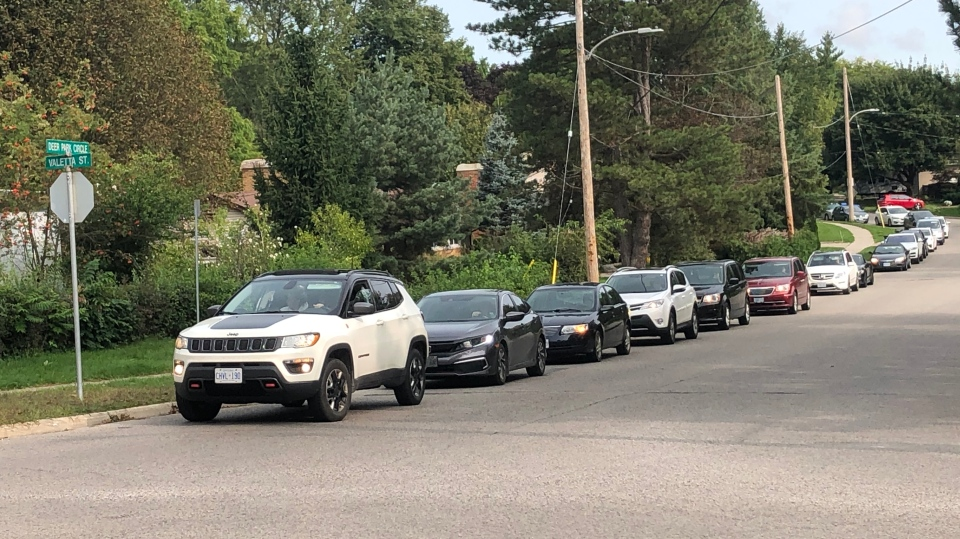 Vehicles are lined up along the street at the Oakridge Assessment Centre in London, Ont. on Monday, Sept. 14, 2020. (Jim Knight / CTV News)
