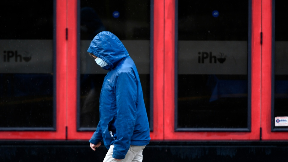 A person walks in the rain in the Byward Market in Ottawa, on Sunday, Sept. 13, 2020, in the midst of the COVID-19 pandemic. THE CANADIAN PRESS/Justin Tang