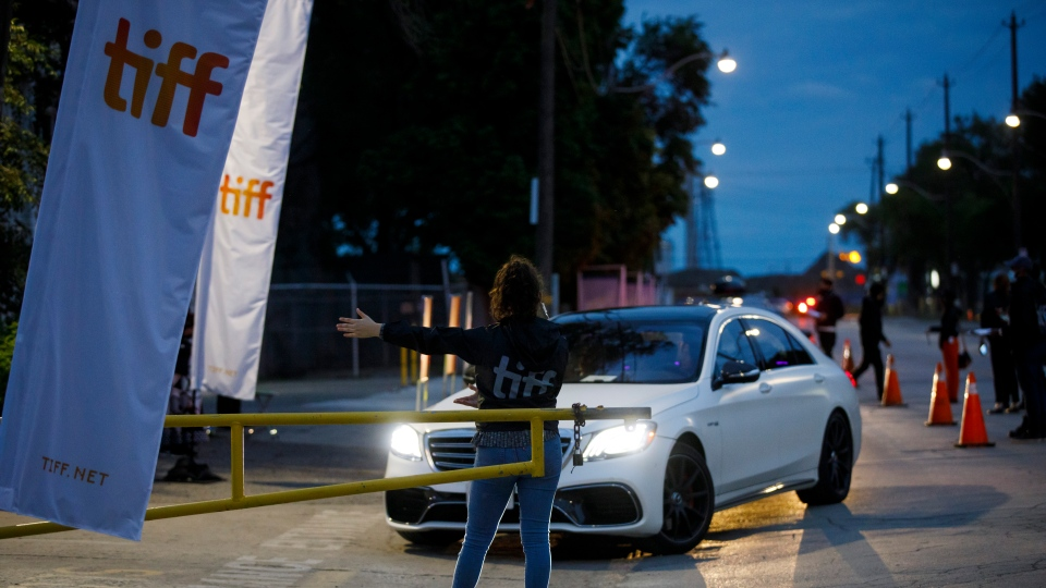An attendant directs a car into Toronto International Film Festival's Visa Skyline Drive-In at CityView venue for the TIFF drive-in premier of David Byrne's American Utopia in Toronto, Thursday, Sept. 10, 2020. THE CANADIAN PRESS/Cole Burston