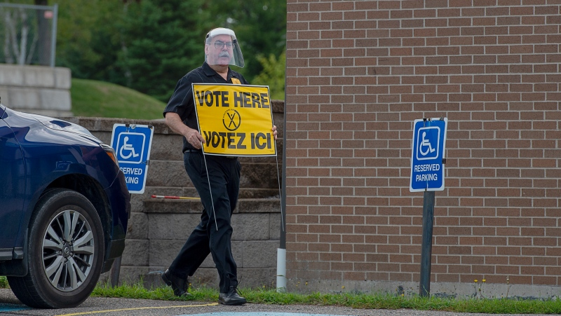 An election worker carries a sign at a voting place for the New Brunswick provincial election in Quispamsis, N.B., Monday, Sept. 14, 2020.  (THE CANADIAN PRESS/Andrew Vaughan)