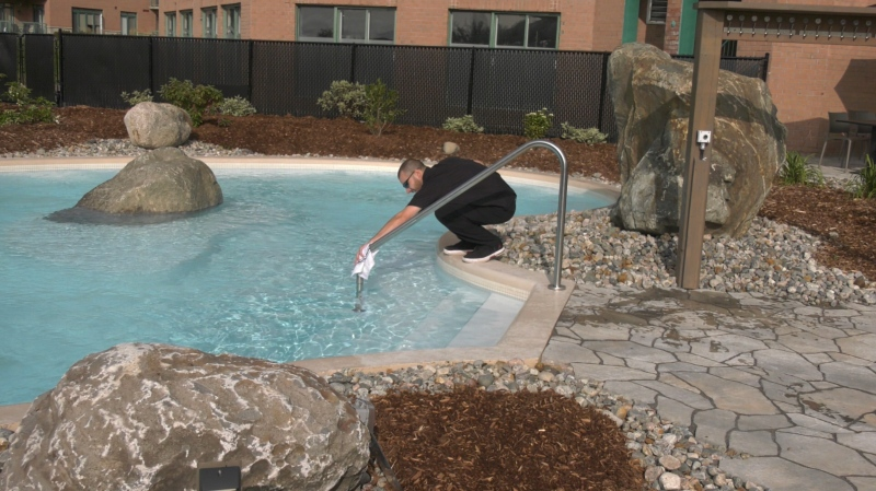 Dominic Morin tests the water at Koena Spa and Nordic Bath in Aylmer, Que. The spa opened Monday, Sept. 14, 2020. (Leah Larocque / CTV News Ottawa)