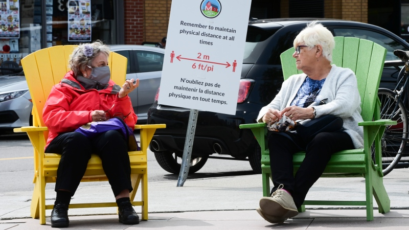 People take a rest in chairs in downtown Ottawa as a sign reminds people to physically distance during the COVID-19 pandemic in Ottawa Monday, Sept. 14, 2020. (Sean Kilpatrick/THE CANADIAN PRESS)