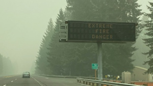 A fire warning sign is seen through the smoke in Sandy, Ore., on Monday, Sept. 14, 2020. (AP Photo/Rachel La Corte)