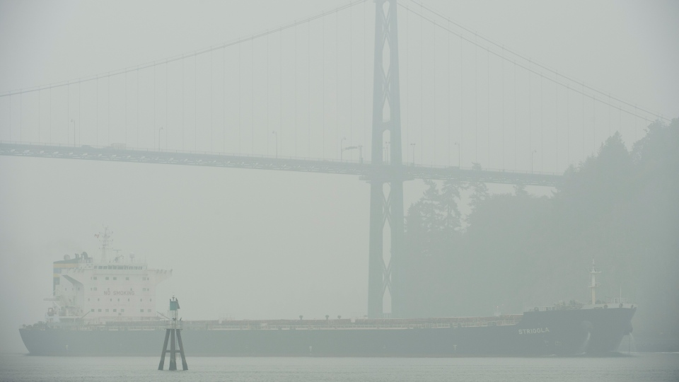 A ship comes through the smokey air as it goes under the Lions Gate Bridge in Vancouver, B.C., Monday, Sept. 14, 2020. THE CANADIAN PRESS/Jonathan Hayward