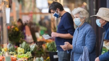 People wear face masks as they shop at a market in Montreal, Sunday, Sept. 13, 2020, as the COVID-19 pandemic continues in Canada and around the world. The Quebec government has introduced fines for individuals caught not wearing face masks or coverings in indoor public spaces. THE CANADIAN PRESS/Graham Hughes