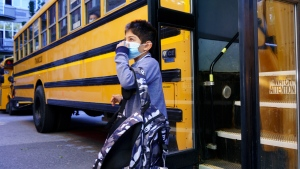 A student adjusts his protective mask as he walks off the bus at the Bancroft Elementary School as students go back to school in Montreal, on Monday, August 31, 2020. THE CANADIAN PRESS/Paul Chiasson