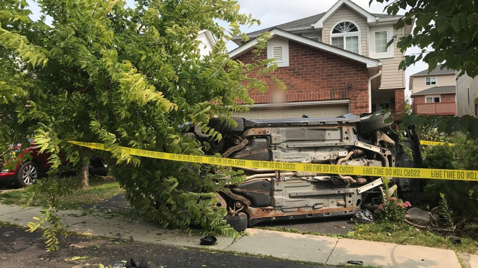 A car on its side in someone's driveway