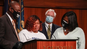 Tamika Palmer, mother of Breonna Taylor, center, speaks during a news conference Tuesday, Sept. 15, 2020 in Louisville, Ky. Beside Palmer is attorney Ben Crump at left and attorney Lonita Baker at right. Palmer briefly spoke at Metro Hall Tuesday afternoon during a press conference to announce a $12 million settlement to Breonna Taylor's estate. Taylor was shot by Louisville police in March during a botched execution of a search warrant. (Matt Stone/Courier Journal via AP)