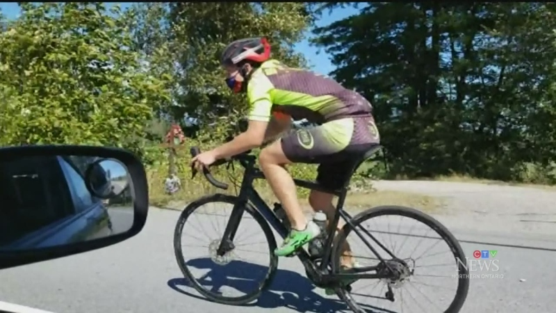 Man riding bike across Canada wearing facemask