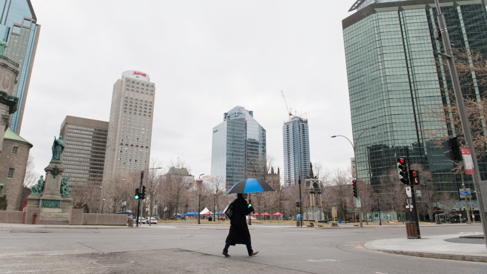 A woman crosses an empty street in downtown Montreal, Sunday, April 5, 2020, as Coronavirus COVID-19 cases rise in Canada and around the world. THE CANADIAN PRESS/Graham Hughes
