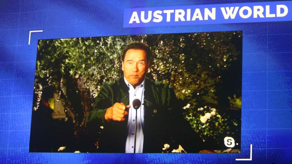 Schwarzenegger is seen on a giant video screen