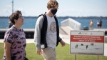 A man wears a mask as people leave the Gord Downie pier after the City of Kingston declared it closed for the season, after people failed to social distance while at the park, in Kingston, Ont., on Saturday, Sept. 5, 2020. The park is now closed due to COVID-19 and there will be a $500 fine for anyone that enters. THE CANADIAN PRESS/Lars Hagberg