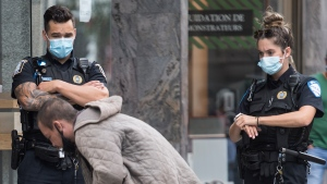 Police look on as they move a homeless man away from a street corner in Montreal, Saturday, August 22, 2020. Quebec's Public Security Department has released guidelines for the province's police forces on street checks to ensure they aren't random, unfounded or discriminatory.THE CANADIAN PRESS/Graham Hughes