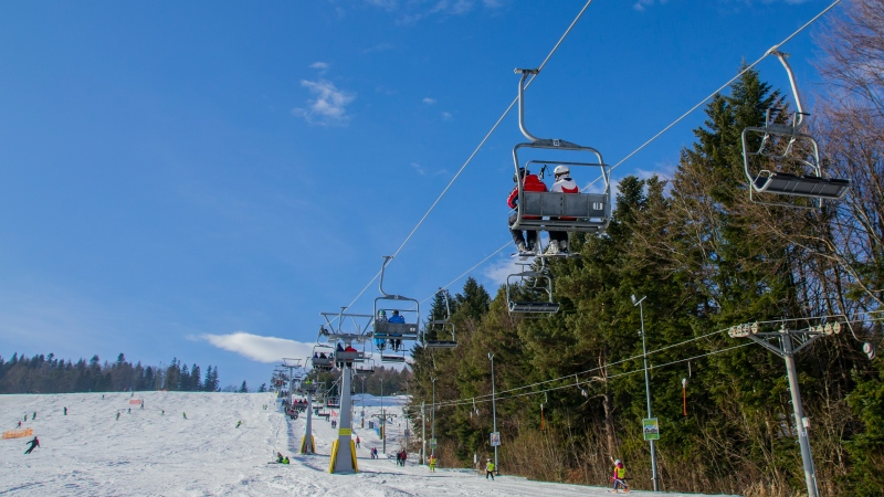 Skiers ride a chairlift at a ski hill. (Pexels/PhotoMIX Company)