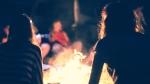 People sit around a campfire. (Shutterstock)