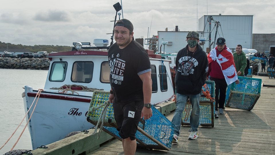Members of the Sipekne'katik First Nation load lobster traps on the wharf in Saulnierville, N.S., after launching its own self-regulated fishery on Thursday, Sept. 17, 2020.  (THE CANADIAN PRESS/Andrew Vaughan)