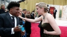 In this Feb. 9, 2020 file photo, Greta Gerwig, right, talks to Jerry Harris on the red carpet at the Oscars at the Dolby Theatre in Los Angeles. (AP Photo/John Locher File)