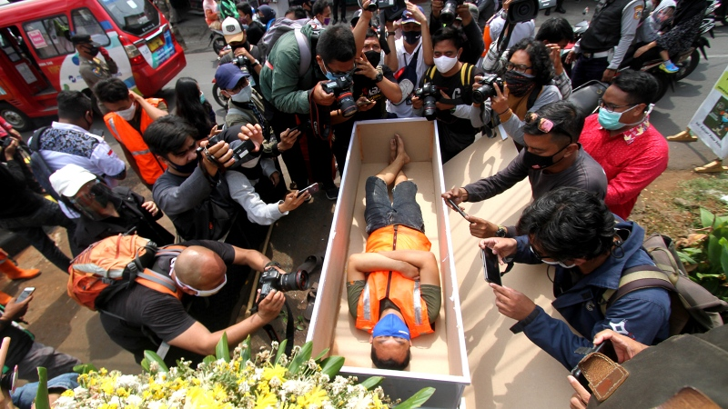 A man caught not wearing a face mask in public lies in a mock coffin while members of the public and the media take pictures as part of punishment by local authorities and enforced by local police in Jakarta on September 3. (Fahmi Dolli/AFP/Getty Images)
