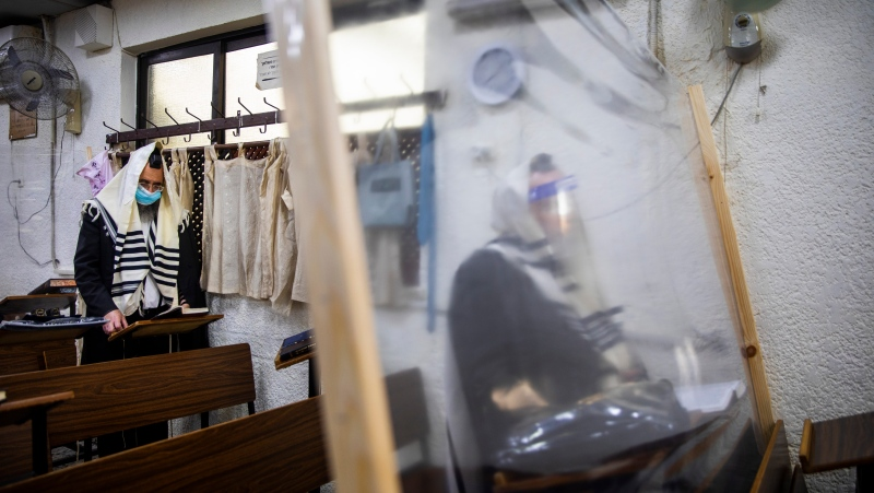 Ultra-Orthodox Jews wearing face masks during a morning prayer in a synagogue separated by plastic partitions, follow new government measures to help stop the spread of the coronavirus, in Bnei Brak, Israel, Friday, Sept 18, 2020. (AP Photo/Oded Balilty)