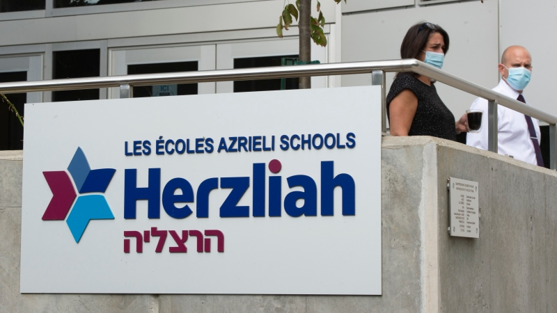 Staff stand outside Herzliah High School Thursday, September 17, 2020 in Montreal. The school is suspending in-person classes for two weeks after more than dozen students and staff tested positive for COVID-19.THE CANADIAN PRESS/Ryan Remiorz