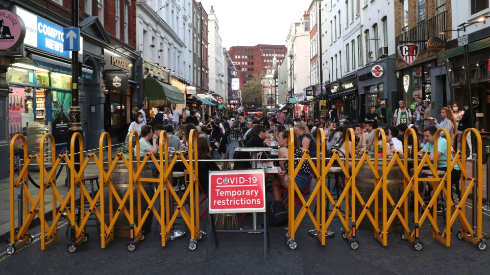 People drink and dine out in Soho, London, Monday Sept. 14, 2020. (Yui Mok / PA via AP)