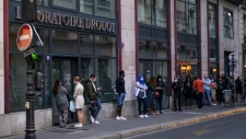 People wearing face masks wait in line in front of a medical laboratory in Paris to get tested for coronavirus. (AFP)