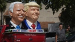 A passerby stops to take a selfie with foam sculpture depictions of U.S. President Donald Trump and Democratic presidential candidate former Vice President Joe Biden along Dixie Highway in Fort Lauderdale, Fla., Thursday, Sept. 3, 2020. (Joe Cavaretta/South Florida Sun-Sentinel via AP)