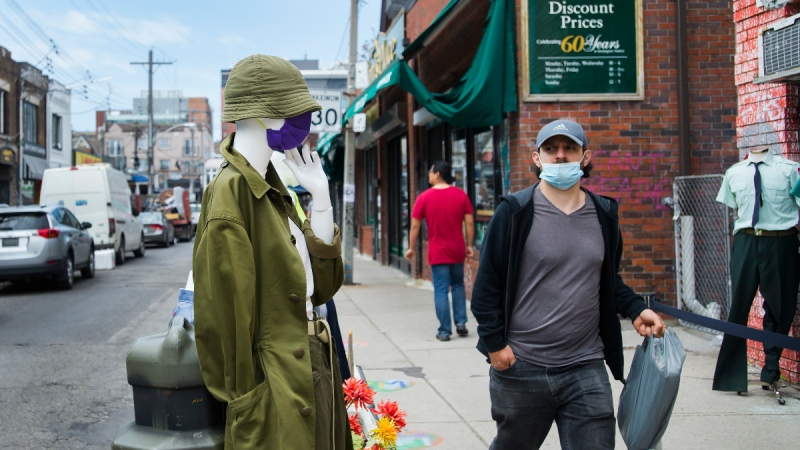 A man walks by a mannequin wearing a mask as store fronts open up for business in Kensington Market during the COVID-19 pandemic in Toronto on June 2, 2020. (THE CANADIAN PRESS / Nathan Denette)