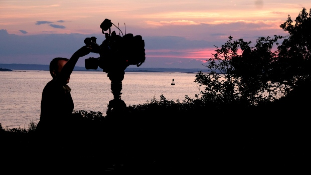 A member of a TV crew adjusts their camera while filming near the shore of Bailey Island, Maine, on July 27, 2020. (Jim Gerberich / AP)