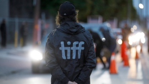 An attendant stands by as cars enter Toronto International Film Festival's Visa Skyline Drive-In at CityView for the TIFF drive-in premier of David Byrne's American Utopia in Toronto, on Sept. 10, 2020. (Cole Burston / THE CANADIAN PRESS)