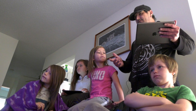 Single-dad Ian Quayle juggles CBE's online-based Hub learning for five of his six children with two iPads to share. From left is Kat, Grade 3, Rayven, Grade 7, Shyla, Grade 2 and bottom right is Blade who is in Grade 6.