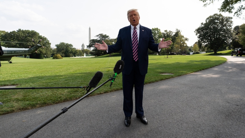 U.S. President Donald Trump speaks with reporters as he walks to Marine One on the South Lawn of the White House, Friday, Sept. 18, 2020, in Washington. Trump is en route to Minnesota. (AP Photo/Alex Brandon)