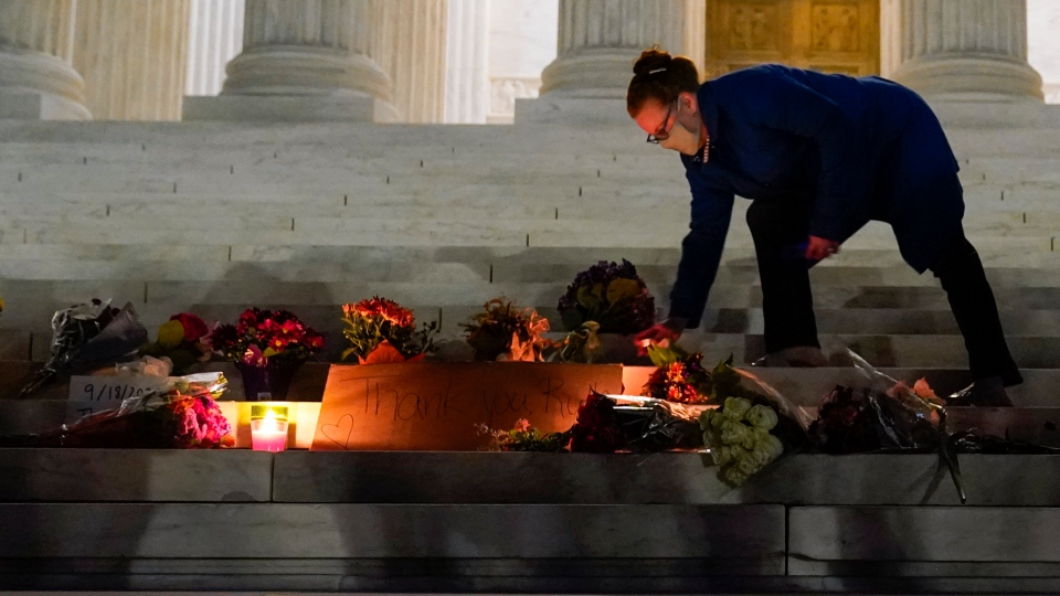 People lay flowers and light candies outside the Supreme Court Friday, Sept. 18, 2020, in Washington, after the Supreme Court announced that Supreme Court Justice Ruth Bader Ginsburg died of metastatic pancreatic cancer at age 87. (AP Photo/Alex Brandon)