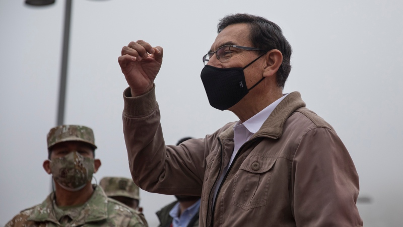 Peru's President Martin Vizcarra talks to doctors and soldiers before the start of house-to-house coronavirus testing in Villa el Salvador, on the outskirts of Lima, Peru, Tuesday, Sept. 15, 2020. (AP Photo/Rodrigo Abd)