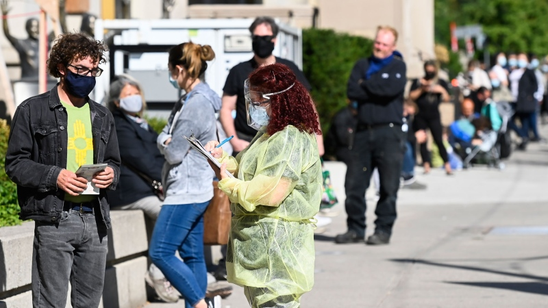 A health-care official takes information as people line up at a COVID assessment centre during the COVID-19 pandemic in Toronto on Friday, September 18, 2020. Ontario is reporting 401 new cases of COVID-19 today, a daily increase not seen since early June.THE CANADIAN PRESS/Nathan Denette