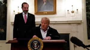 U.S. President Donald Trump signs an $8.3 billion bill to fight the coronavirus outbreak in the U.S., Friday, March 6, 2020 at the White House in Washington, as Department of Health and Human Services Secretary Alex Azar, looks on. (AP Photo/Evan Vucci)