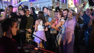 People are seen dancing to a busker in Leicester Square, central London, on September 12, days before social gatherings were restricted again. (Peter Summers/Getty Images)