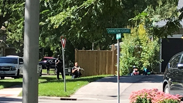 Officers with guns can be seen on Chancton Court on Saturday, Sept. 19, 2020.