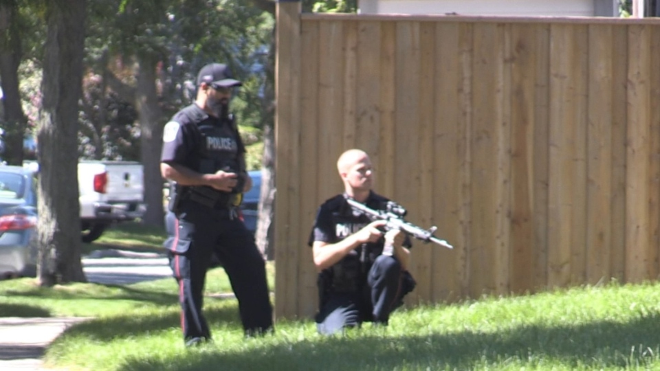 An officer with a gun can be seen on Chancton Court in London, Ont. on Saturday, Sept. 19, 2020. (Sean Irvine / CTV London)