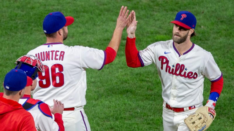 Philadelphia Phillies closing pitcher Tommy Hunter, left, his fives right fielder Bryce Harper, right, after their team defeated the Toronto Blue Jays in a baseball game, Saturday, Sept. 19, 2020, in Philadelphia. (AP Photo/Laurence Kesterson)