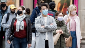 People wear face masks as they wait cross a street in Montreal, Saturday, September 19, 2020, as the COVID-19 pandemic continues in Canada and around the world. THE CANADIAN PRESS/Graham Hughes