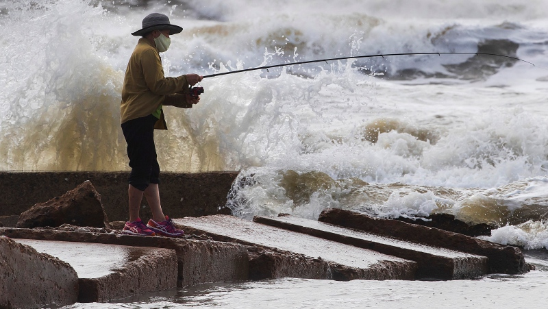 Waves crash as Houston resident Tinh Pham fishes from the rocks at Diamond Beach on the west end of the Galveston Seawall in Galveston, Texas on Saturday, Sept. 19, 2020. (Stuart Villanueva/The Galveston County Daily News via AP)